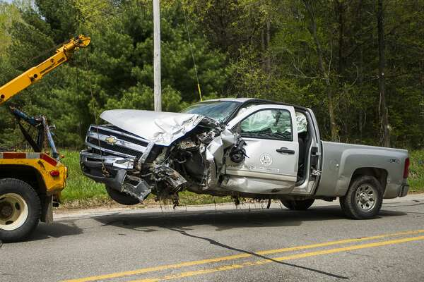 A tow truck pulls a Midland County Drain Commission vehicle from the scene after it was involved in a crash on N. West River Road near Gage Road in Sanford on Tuesday, May 21, 2019. According to Captain Tracy Thomas of the Midland County Sheriff's Office, the driver suffered minor injuries. (Katy Kildee/kkildee@mdn.net)