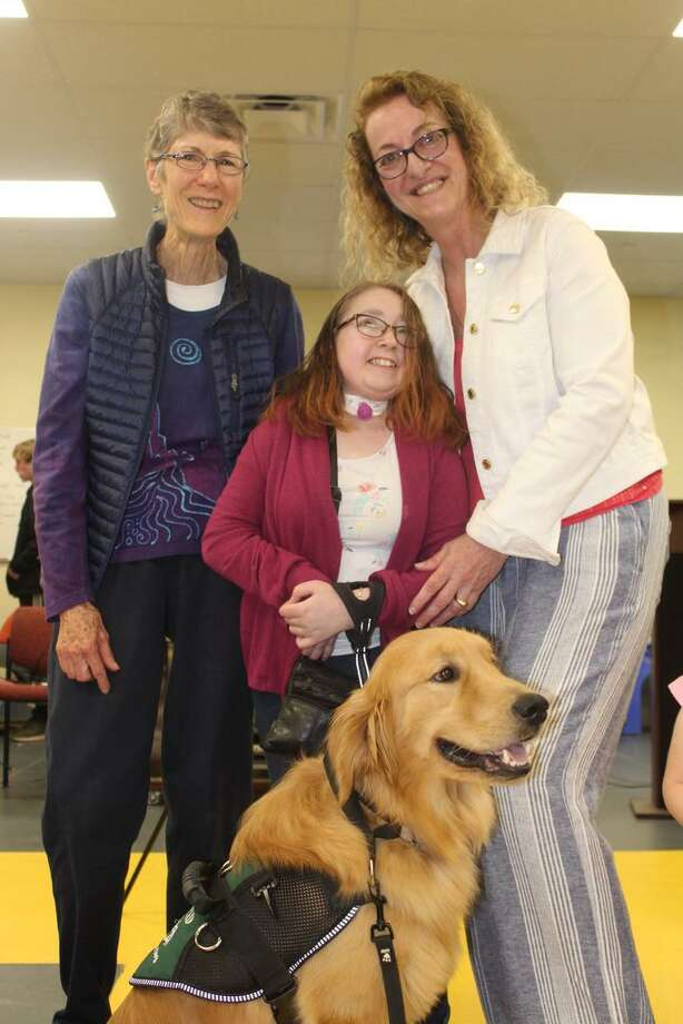 Hailey Giguere, center, of Windsor, and her Service Dog Honor were one of three teams to graduate from ECAD's spring team training class on May 8 in Torrington. Giguere suffers from hemiparesis and has difficulty walking on her own. Honor will help Giguere with balance and mobility. Katharine Brunkhorst, left, of Pittsburgh and Lu Picard, right, ECAD's co-founder and director of programs, congratulate Giguere. Photo: Contributed Photo