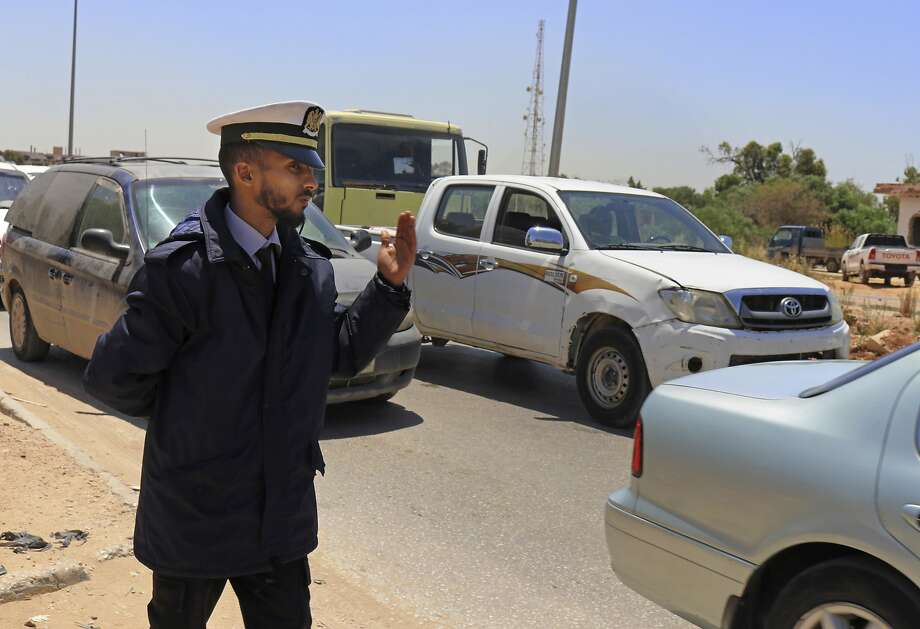 A police officer waves vehicles through a checkpoint during rush hour in Benghazi, Libya. Photo: Rami Musa / Associated Press