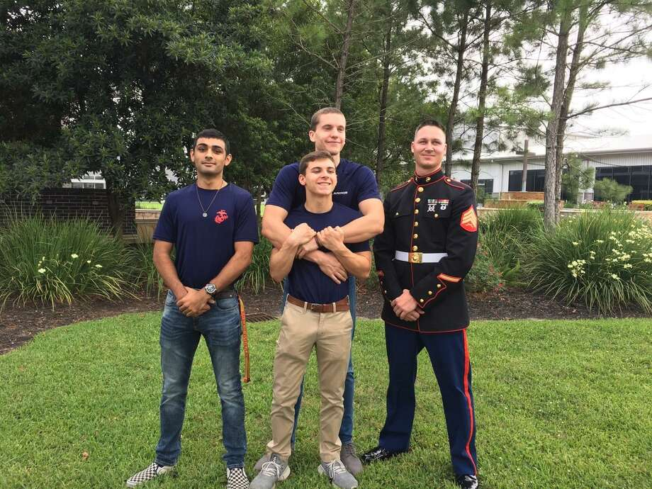 U.S. Marine recruiter Sgt. Zachary Head, right, said he expects the world of his new recruits because of their high qualifications. He added that he also expects them each to become squad leaders and called them the new face of the Marine Corps. The recruits are, from left, Rohan Misra, Daniel Aldric, in back, and Michael Fontenot. Photo: Karen Zurawski / Karen Zurawski