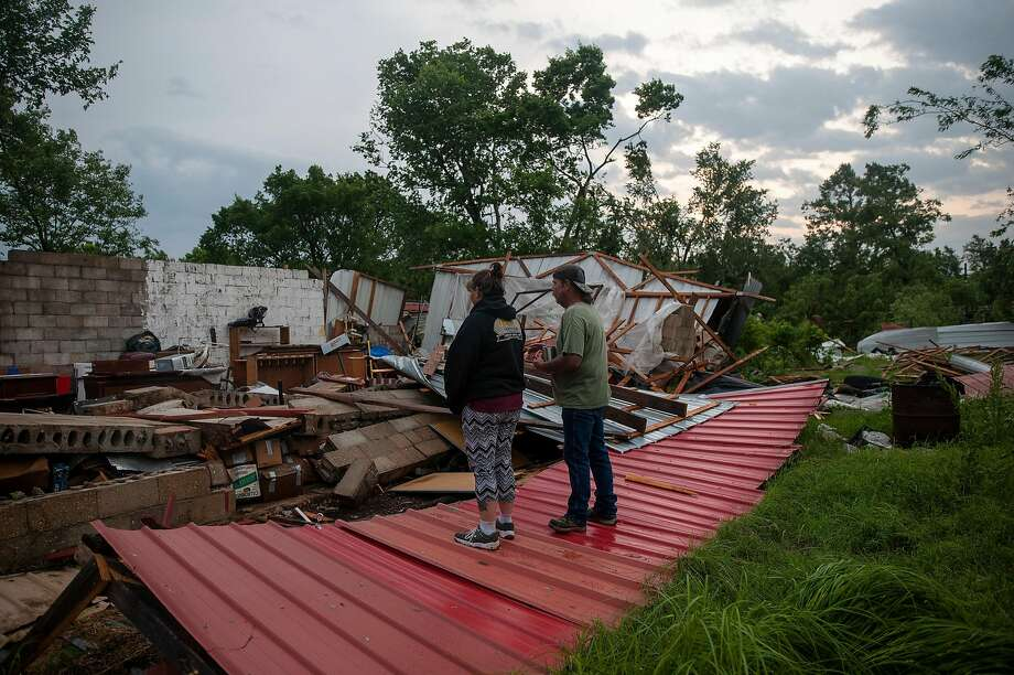 Roy and Kimberly Reed survey their home, destroyed by a tornado in Peggs, Okla., Severe thunderstorms struck parts of Texas and Oklahoma, producing short-lived tornadoes. Photo: Joseph Rushmore / New York Times