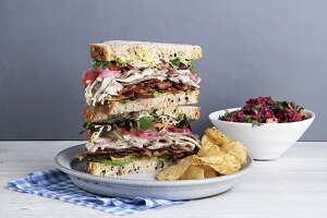 The towering 'Farm Club' sandwich at sandwich at Mendocino Farms is stacked with roasted free range turkey breast, smashed avocado, smoked bacon, herb aioli, tomatoes, greens, and pickled red onions.