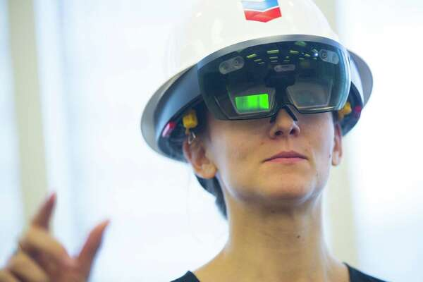 Katherine Blunt tries to use augmented reality technology through the Microsoft HoloLens, Monday, Oct. 1, 2018 in downtown Houston.