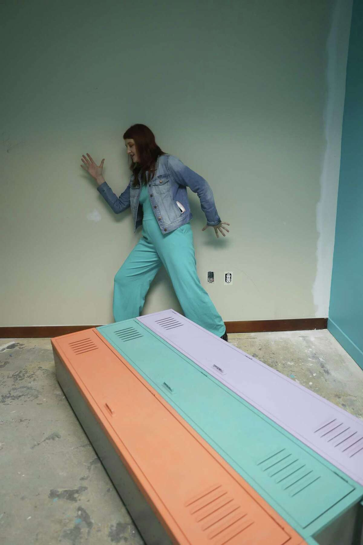 """FOMO Factory founder Rachel Youens demonstrates how a wall in the """"glow room"""" will work while on a tour in the FOMO Factory under construction in the Galleria mall, in Houston , Thursday, May 2, 2019. FOMO Factory was formerly in Austin, and is set to open in Houston in June. Malls and department stores are incorporating Instagrammable, experiential retail to draw customers in the age of Amazon."""