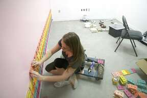 Amber Oliver places painted cassette tapes on the wall in one of the rooms in the FOMO Factory under construction in the Galleria mall, in Houston , Thursday, May 2, 2019. FOMO Factory was formerly in Austin, and is set to open in Houston in June. Malls and department stores are incorporating Instagrammable, experiential retail to draw customers in the age of Amazon.