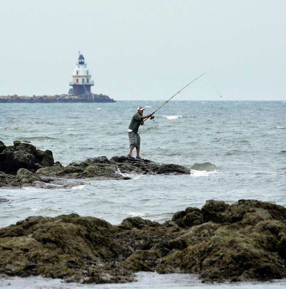 Ivan Perez of New Haven casts his line off the rocks at Lighthouse Point Park as he was fishing for Porgies. Photo: Peter Casolino