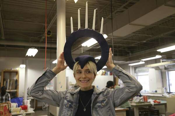 Montana Priest tries on a crown as she works on her costume Tuesday at the Southwest School of Art. Students from the school will participate in Saturday's Lone Star Parade.