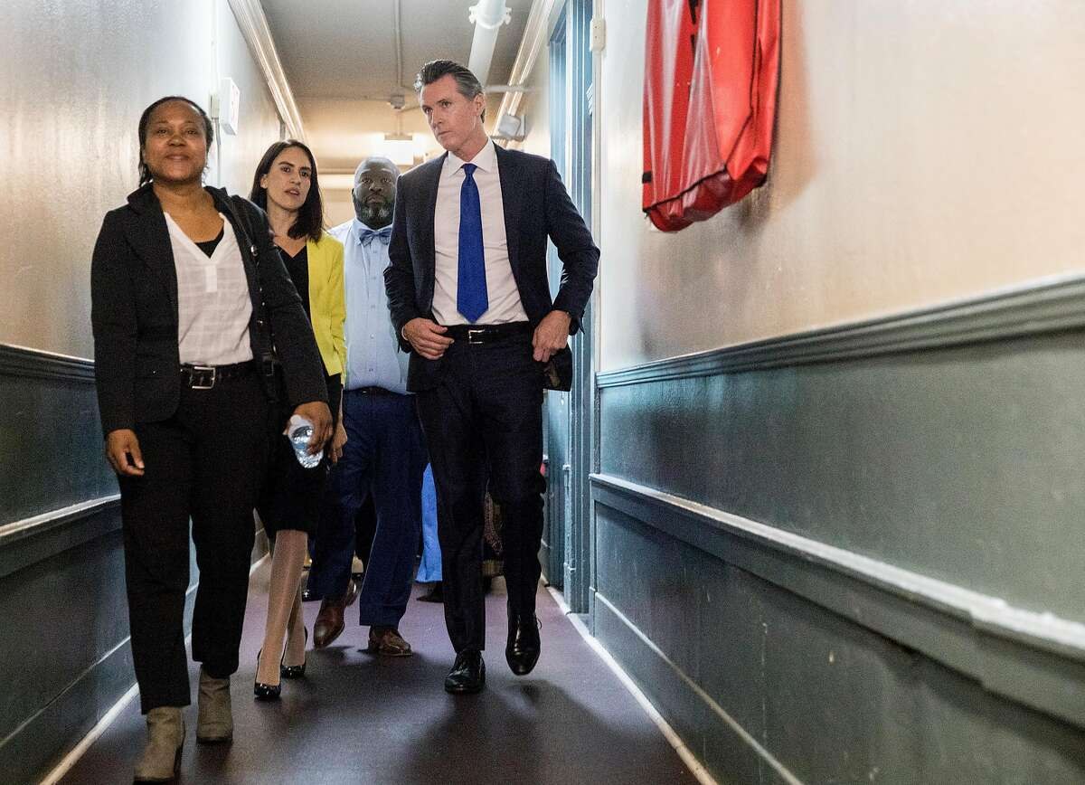 California Governor Gavin Newsom tours rooms at the the Henry Robinson Multi-Service Center with former resident Tekel Carlisle, 42, (left) before a press conference announcing a newly created state-level homeless commission alongside Oakland Mayor Libby Schaaf and other Alameda County and state officials in Oakland, Calif. Tuesday, May 21, 2019.