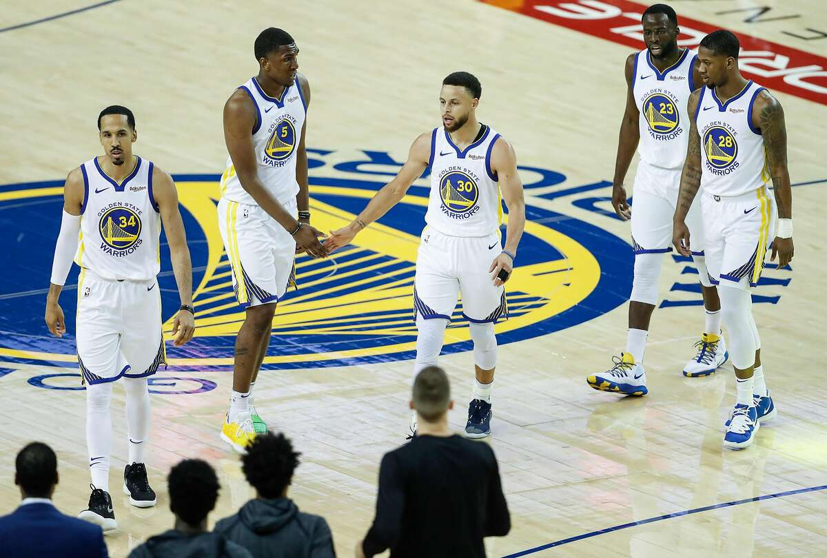 Golden State Warriors Shaun Livingston, Kevon Looney, Stephen Curry, Draymond Green, and Alfonzo McKinnie walk back to the bench during a break in the action in the first quarter during game 1 of the Western Conference Finals between the Golden State Warriors and the Portland Trail Blazers at Oracle Arena on Tuesday, May 14, 2019 in Oakland, Calif.