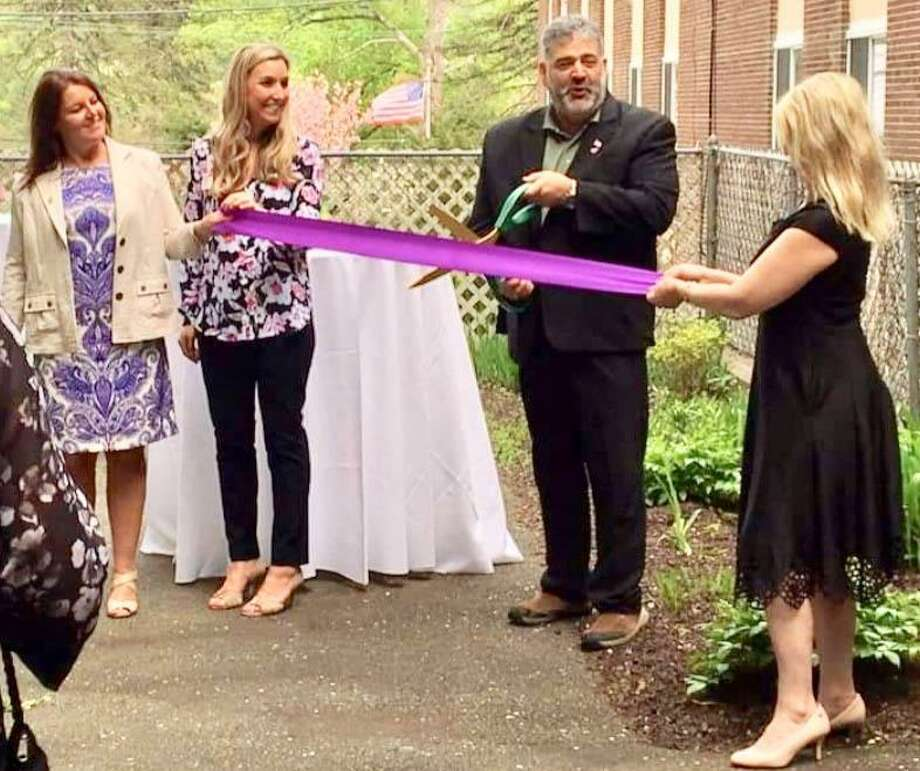 Village Crest Center for Health & Rehabilitation in New Milford on May 7 held an open house and a ribbon-cutting ceremony celebrating the opening of its new memory care unit. Above, New Milford Mayor Pete Bass prepares to cut the ribbon alongside, from left to right, Carolyn DeRocco, vice president of education and programs for the Alzheimer's Association, Erin Healy, administrator at Village Crest, and Julie A. Brown, director of business development for National Health Care Associates Inc. Photo: Contributed Photo / Contributed Photo / The News-Times Contributed