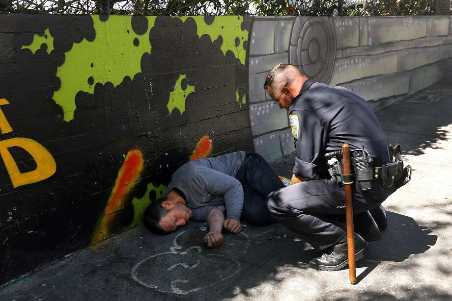 Officer Brian Donohue checks on Jeffrey Choate after he sees him lying on the sidewalk along Larkin Street and before asking him to dispose of used needles next to him in a proper container on Monday, September 10,  2018 in San Francisco, Calif. Photo: Lea Suzuki / The Chronicle 2018