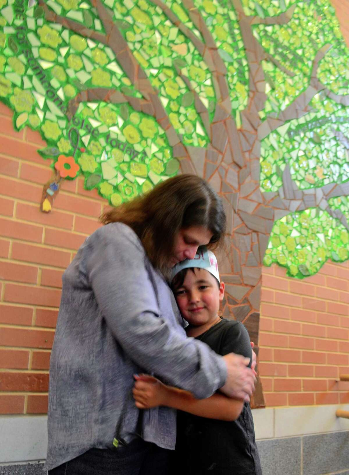 """Student Shane Moonesar, 6, gets a hug from Jane Adams from Ben's Bells after the Kindness Club's Kindness Tree mural was unveiled at Frenchtown Elementary School in Trumbull, Conn., on Tuesday May 21, 2019. Ben's Bells """"be kind"""" murals are a series of kindness-themed mosaic murals created by local artists, students, and community members. Shane was one of the helpers to Jane in the making of the mural with many of his fellow students."""
