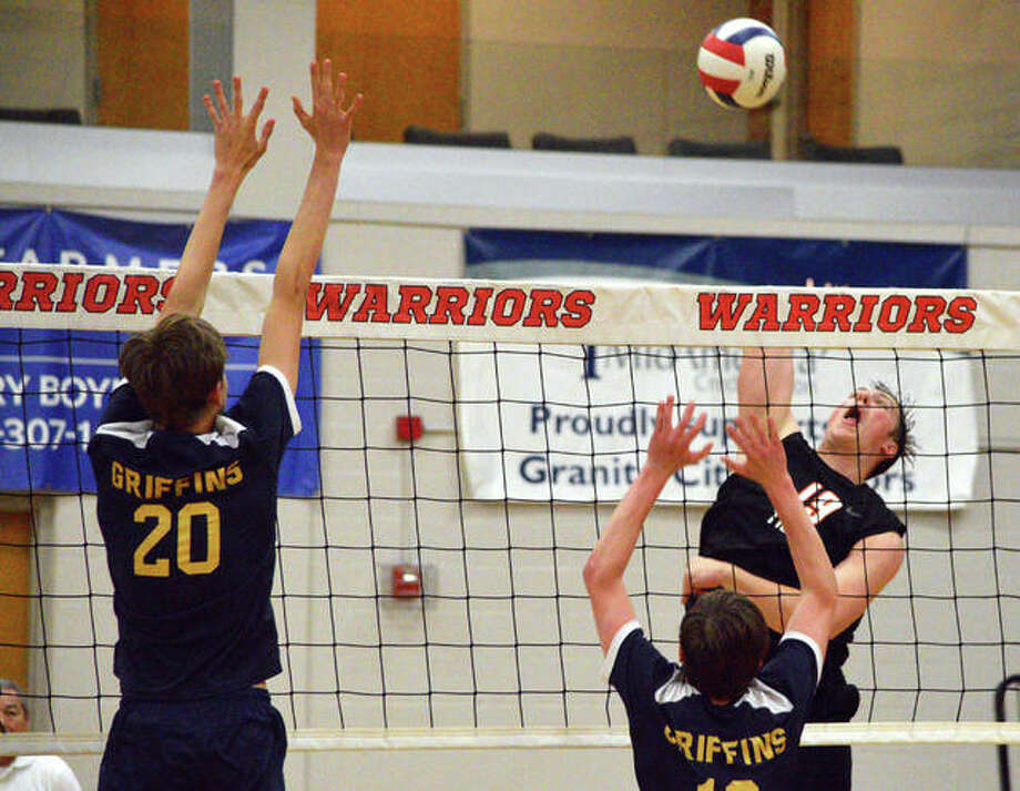 Edwardsville's Josh Whittenburg, right, goes up for a kill against Father McGivney's Caleb Tanzyus during Tuesday's semifinal match in the Granite City Regional. Photo: Scott Marion/The Intelligencer