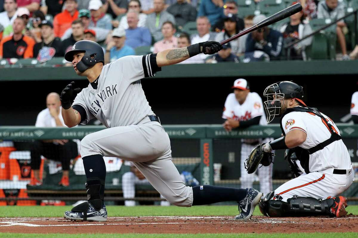 BALTIMORE, MARYLAND - MAY 21: Gary Sanchez #24 of the New York Yankees follows his three RBI home run as catcher Austin Wynns #61 of the Baltimore Orioles looks on in the first inning at Oriole Park at Camden Yards on May 21, 2019 in Baltimore, Maryland. (Photo by Rob Carr/Getty Images)