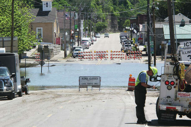 Illinois Route 100 remained closed Monday at Illinois 3 in Grafton, but workers were busy cleaning up and repairing flood damage in anticipation of the Memorial Day weekend. A secondary crest is predicted for early Sunday morning and could impact travel.