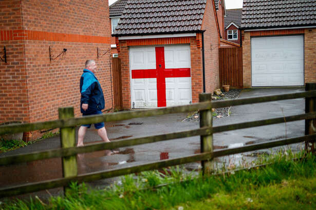 A man walks past a garage decorated with a Saint George's Cross in Holbeach, England, on May 8, 2019.