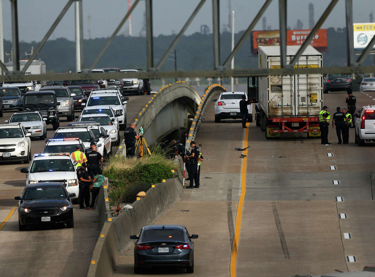 Officials investigate the scene of a fatal vehicle crash, where a car flipped off the East Freeway and into the San Jacinto River Wednesday, May 22, 2019, in Lynchburg, Texas.