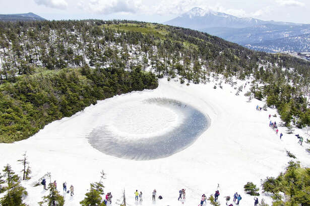 """A natural phenomenon called the """"dragon's eye"""" appears Wednesday at Kagaminuma pond near the top of 1,613-meter Mt. Hachimantai on the border between Iwate and Akita prefectures in Japan. In spring, snowmelt flows into the pond, which has a diameter of about 50 meters, and remains on the edge. Meanwhile, the snow accumulated near the center remains unmelted, creating a landscape resembling the eye of a dragon."""