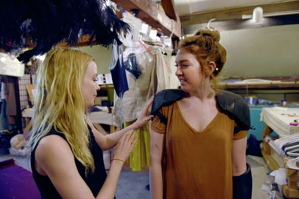 Cutter and draper Emily Mays, left, examines a potential costume for Camelot on costume shop manager Alison Zador.