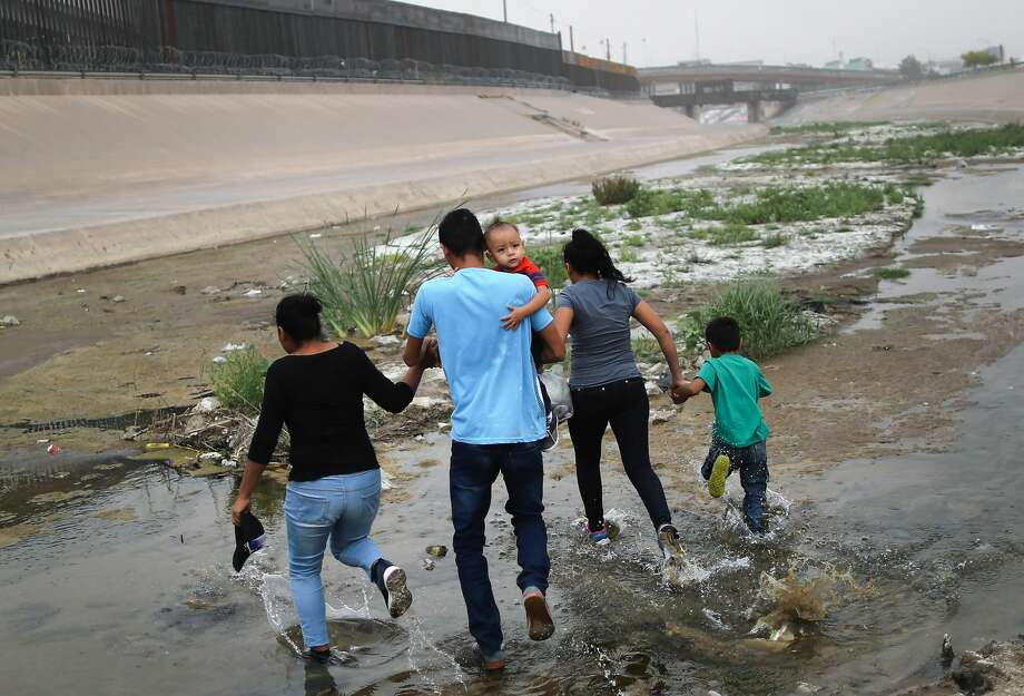 CIUDAD JUAREZ, MEXICO - MAY 20:  Migrants hold hands as they cross the border between the U.S. and Mexico at the Rio Grande river, on their way to enter El Paso, Texas, on May 20, 2019 as taken from Ciudad Juarez, Mexico. The location is in an area where migrants frequently turn themselves in and ask for asylum in the U.S. after crossing the border.  Approximately 1,000 migrants per day are being released by authorities in the El Paso sector of the U.S.-Mexico border amidst a surge in asylum seekers arriving at the Southern border.  (Photo by Mario Tama/Getty Images) Photo: Mario Tama/Getty Images