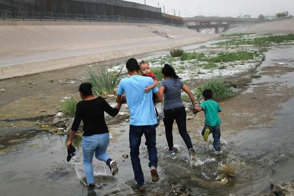CIUDAD JUAREZ, MEXICO - MAY 20: Migrants hold hands as they cross the border between the U.S. and Mexico at the Rio Grande river, on their way to enter El Paso, Texas, on May 20, 2019 as taken from Ciudad Juarez, Mexico. The location is in an area where migrants frequently turn themselves in and ask for asylum in the U.S. after crossing the border. Approximately 1,000 migrants per day are being released by authorities in the El Paso sector of the U.S.-Mexico border amidst a surge in asylum seekers arriving at the Southern border. (Photo by Mario Tama/Getty Images)