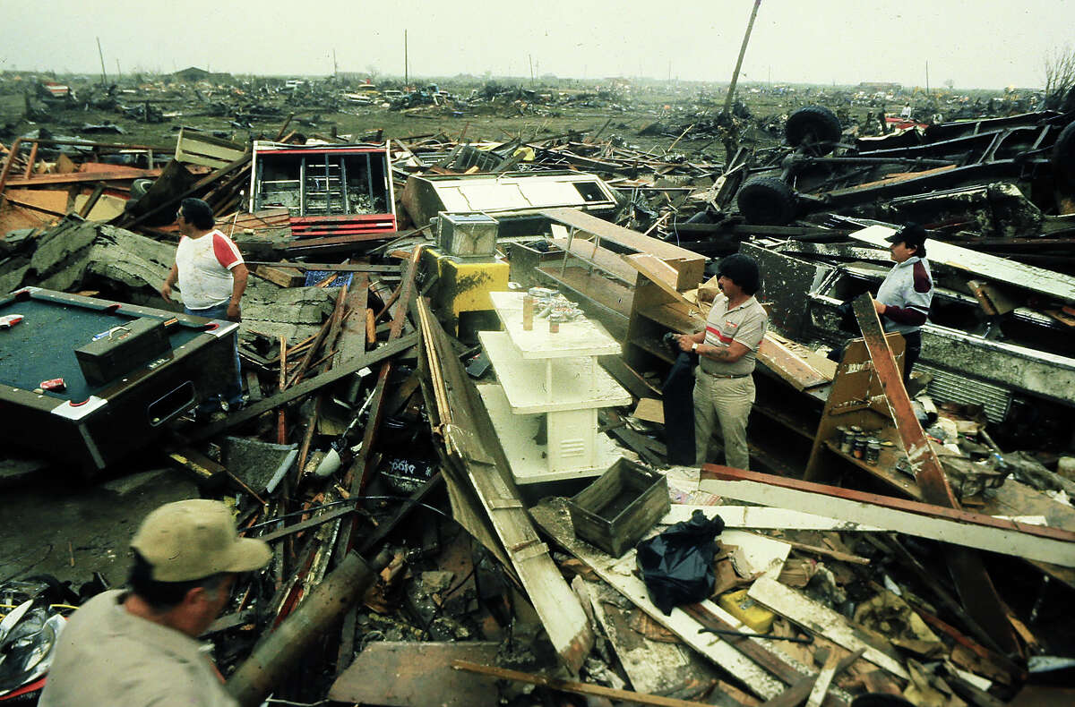 The Gallego family, Joe, left, and son Jim, right search for valuables in the bar that they built, destroyed by the Saragosa, Texas tornado, May 22, 1987.