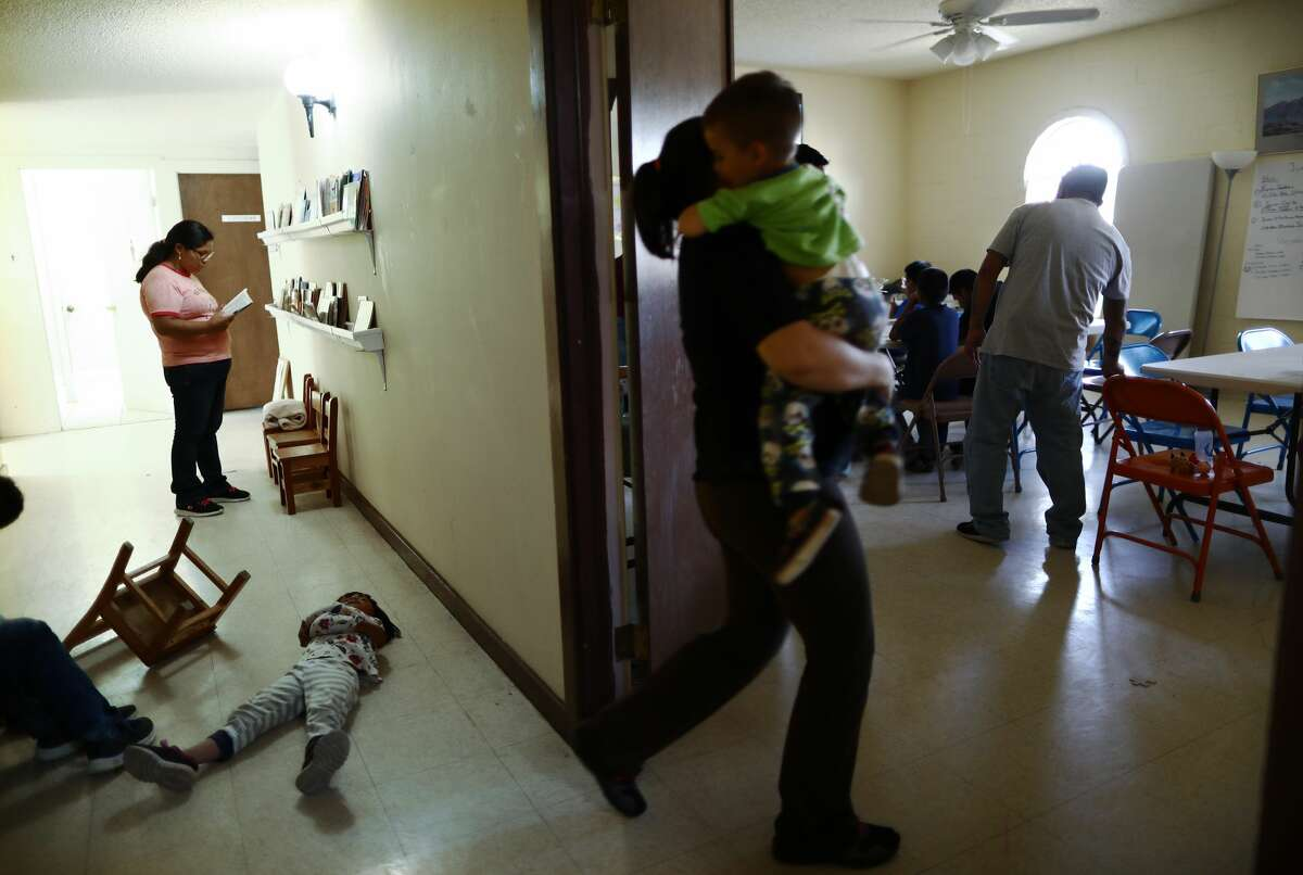 Migrants gather as a child plays on the floor in a church shelter for migrants who seek asylum on May 16 in Las Cruces, N.M.. After being released by the U.S. Immigration and Customs Enforcement to the shelter, asylum-seekers are then normally transferred from the shelter to their U.S. sponsors as they await their asylum requests. Approximately 1,000 migrants per day are being released by authorities in the El Paso sector of the U.S.-Mexico border, which includes Las Cruces. Las Cruces has processed over 5,000 asylum seekers since it began receiving them from the Border Patrol on April 12.