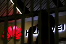 A man walks by a Huawei retail shop behind a handrail inside a commercial office building in Beijing, Tuesday, May 21, 2019. The Trump administration's sanctions against Huawei have begun to bite even though their dimensions remain unclear. U.S. companies that supply the Chinese tech powerhouse with computer chips saw their stock prices slump Monday, and Huawei faces decimated smartphone sales with the anticipated loss of Google's popular software and services. (AP Photo/Andy Wong)
