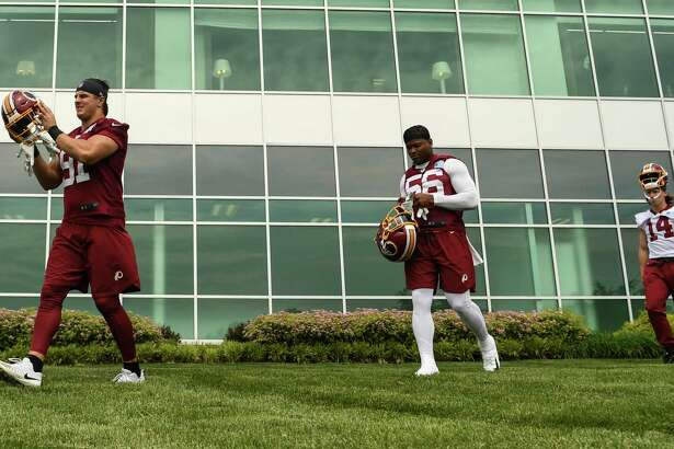 Linebacker Reuben Foster, center, runs onto the field before Redskins practice Monday.