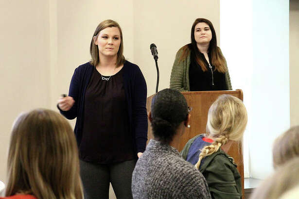 SIUE senior psychology majors Ashley Monier, front, and Abigail Haloftis, back, taught the importance of forgiveness at the Conversation Toward a Brighter Future conference.