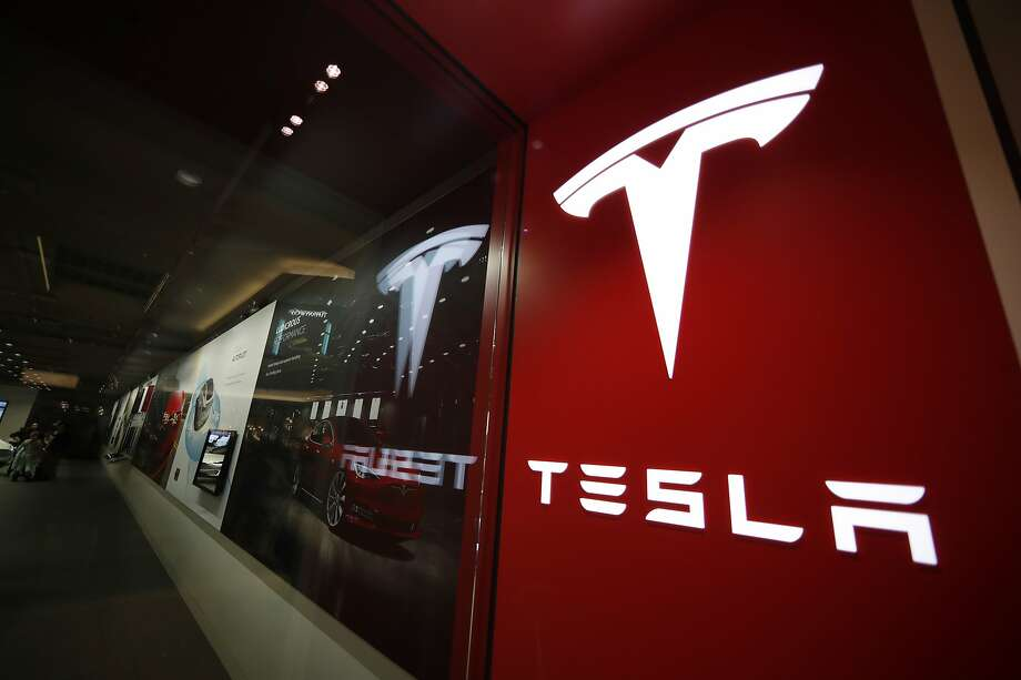FILE- In this Feb. 9, 2019  file photo, a sign bearing the company logo is displayed outside a Tesla store in Cherry Creek Mall in Denver.  Photo: David Zalubowski, Associated Press