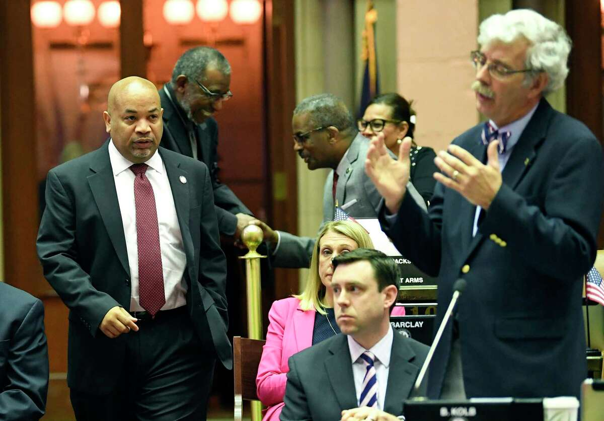 Assembly Speaker Carl Heastie, D-Bronx, left, walks on the Assembly floor as Assemblyman Andy Goodell, R-Jamestown ,right, speaks to members of the New York state Assembly against legislation that authorizes state tax officials to release, if requested, individual New York state tax returns to Congress during a vote in the Assembly Chamber at the state Capitol Wednesday, May 22, 2019, in Albany, N.Y.
