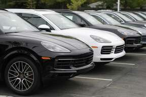 FILE--In this Sunday, May 19, 2019, file photograph, a line of unsold 2019 Cayenne sports-utility vehicles sits at a Porsche dealership in Littleton, Colo. (AP Photo/David Zalubowski)