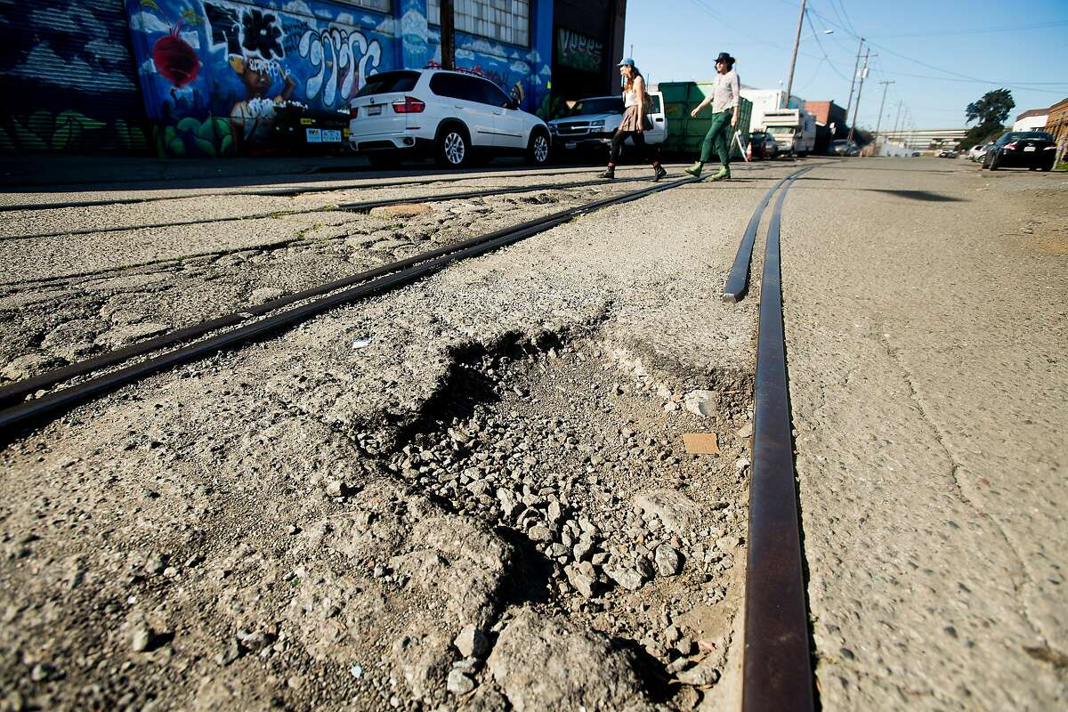 Pedestrians pass a pothole on 18th St. in Oakland, Calif., on Saturday, Feb. 3, 2018.