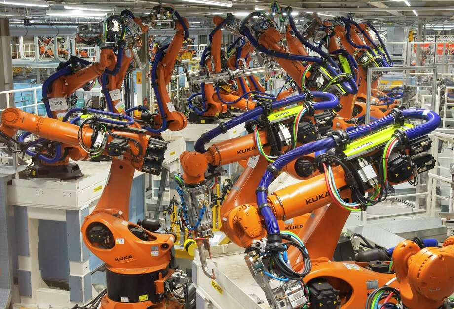 In this Tuesday, May 14, 2019 photo, robot arms stand at the assembly line during the reconstruction for the electrical car body construction at a press tour at the plant of the German manufacturer Volkswagen AG (VW) in Zwickau, Germany. Volkswagen will total shift into electric cars at the plant in Zwickau and the first vehicles are to roll off the assembly line at the end of 2019. (AP Photo/Jens Meyer) Photo: Jens Meyer / Copyright 2019 The Associated Press. All rights reserved.