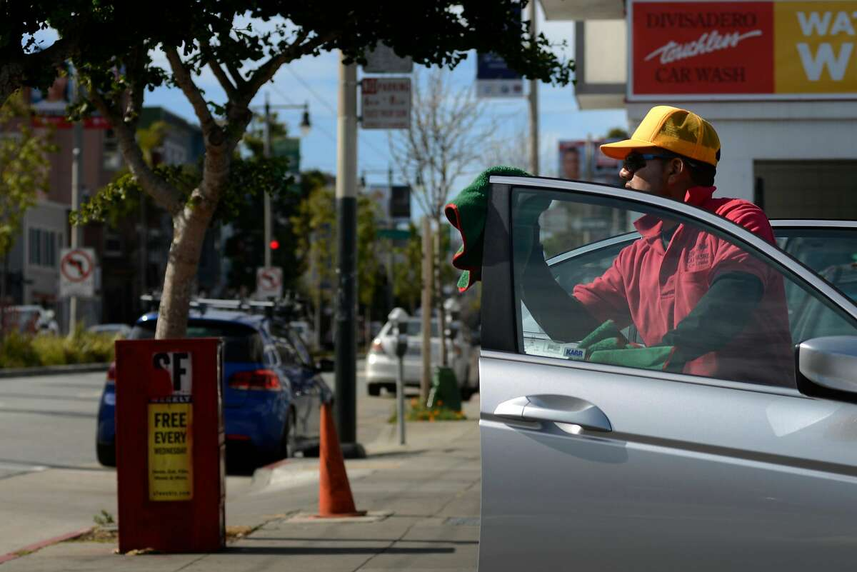 Employees of Divisadero Touchless car wash dry and polish cars in San Francisco, California, on Tuesday, June 30, 2015.