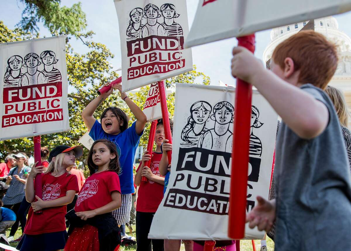 Students from Melrose Leadership Academy carry sings during a rally and march held at the California State Capitol by public school teachers, administrators and supports urging state legislators to provide more funding for public schools in Sacramento, Calif. Wednesday, May 22, 2019.