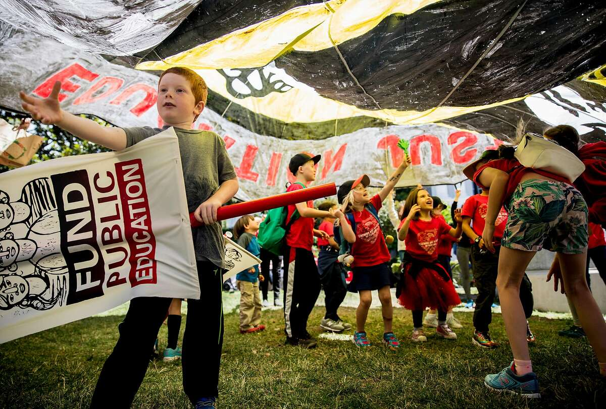Students from Melrose Leadership Academy in Oakland play underneath a large banner during a march and rally held at the California State Capitol by public school teachers, administrators and supports urging state legislators to provide more funding for public schools in Sacramento, Calif. Wednesday, May 22, 2019.
