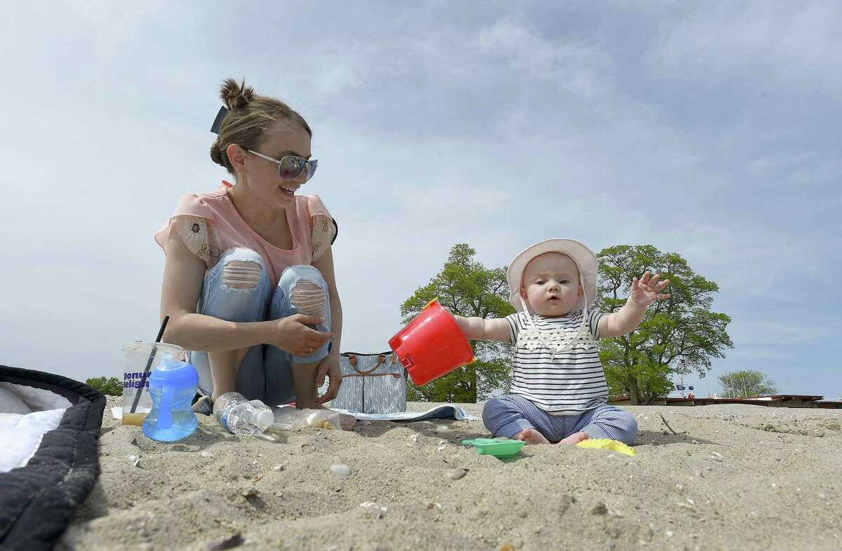 Ludmyla Markevych, of Stamford, plays with her daughter Emily Matselivkh at Cove Island Beach on Wednesdayin Stamford. The City of Stamford Board of Representatives recently passed a resolution that allows veterans and their spouses to park for free at city beaches this summer.