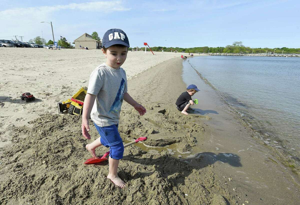Michael Alatortsev, of Stamford, and his brother, Paul, play in the sand at West Beach on Wednesdayin Stamford. The two came to the beach to enjoy the afternoon with their mother after she picked up the summer beach passes at the Stamford Government Center.