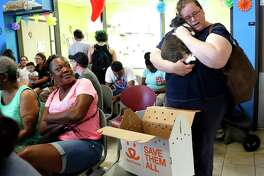 Katrina Hardeman hugs her newly adopted 4-year-old cat, Noonie, at the Harris County Animal Shelter, where hundreds of people lined up for hours to adopt or foster animals with reduced adoption fees to $10 for all animals, Wednesday, May 22 through Friday, May 24, 2019. In less than 48 hours, Harris County Animal Shelter has taken in from the community over 200 animals to the already overcrowded facility. With reduced adoption fees, and provide supplies if needed to Harris County residents willing to foster animals. Adoption fee includes spay or neuter procedure, all age appropriate vaccines, a microchip and a one-year pet license.