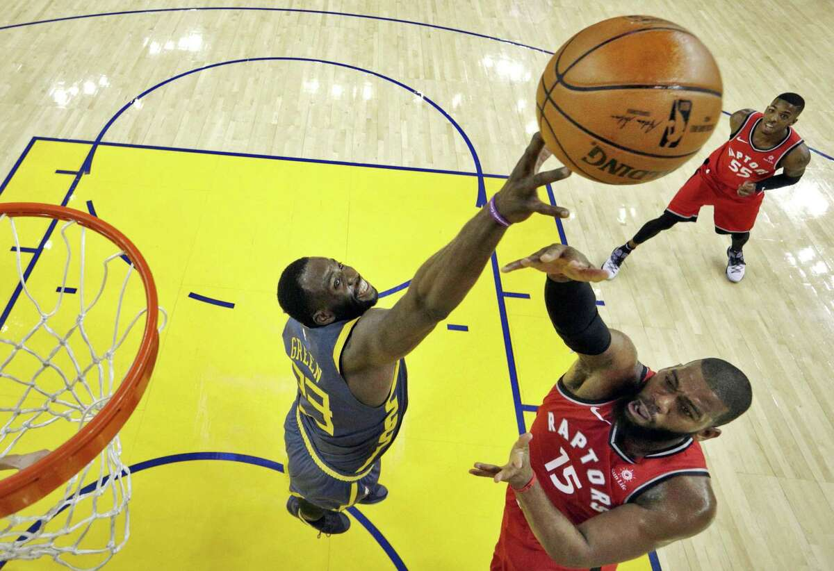 Draymond Green (23) blocks a shot by Greg Munroe (15) in the second half as the Golden State Warriors play the Toronto Raptors at Oracle Arena in Oakland, Calif., on Wednesday, December 12, 2018.