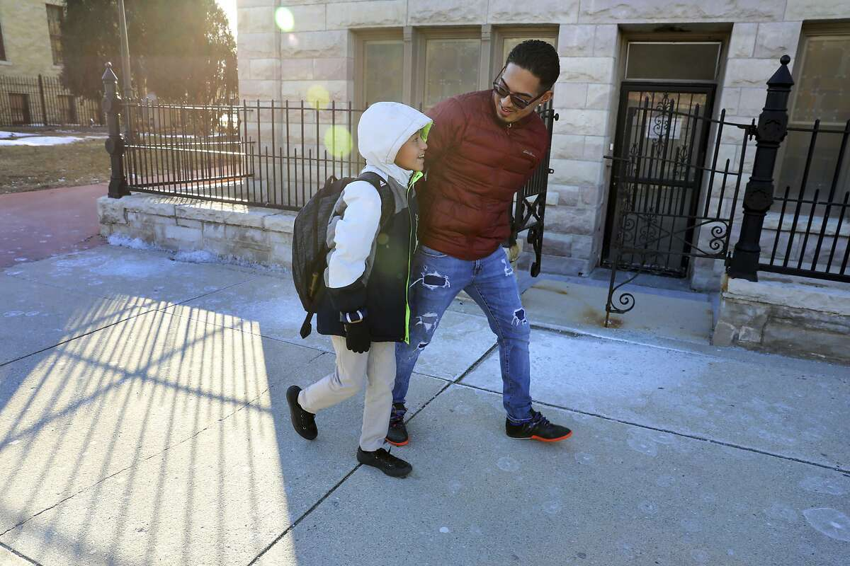 In this Feb. 8, 2019 photo, Erick Gamboa picks up his son Gerald Hernandez, 10, from St. Anthony School in Milwaukee a week after being released from the Kenosha County Detention Center in Kenosha, Wis. Gamboa's six months in immigration detention was a hardship on his family of five. Unlike most immigrants, Gamboa had a lawyer to argue his case. Statistics show immigrants have a much lower chance of deportation if they have a lawyer. (Coburn Dukehart/Wisconsin Center for Investigative Journalism via AP)