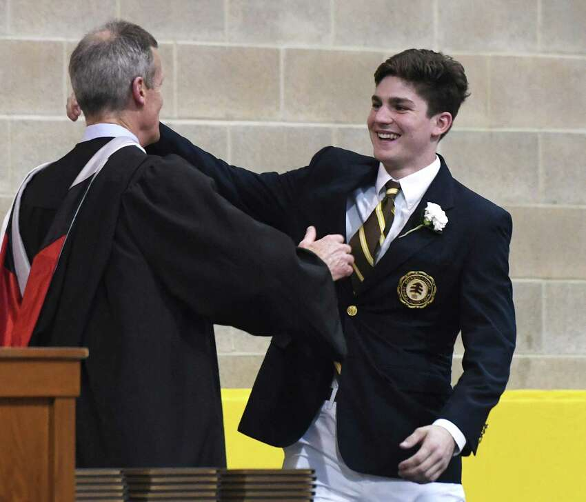 Cooper Moore hugs Headmaster Thomas Philip before accepting his diploma at the Brunswick School 117th Commencement at Brunswick's School's Dann Gymnasium in Greenwich, Conn. Wednesday, May 22, 2019. Retired Supreme Court Associate Justice Anthony M. Kennedy gave the commencement speech before 100 new graduates walked across the stage.