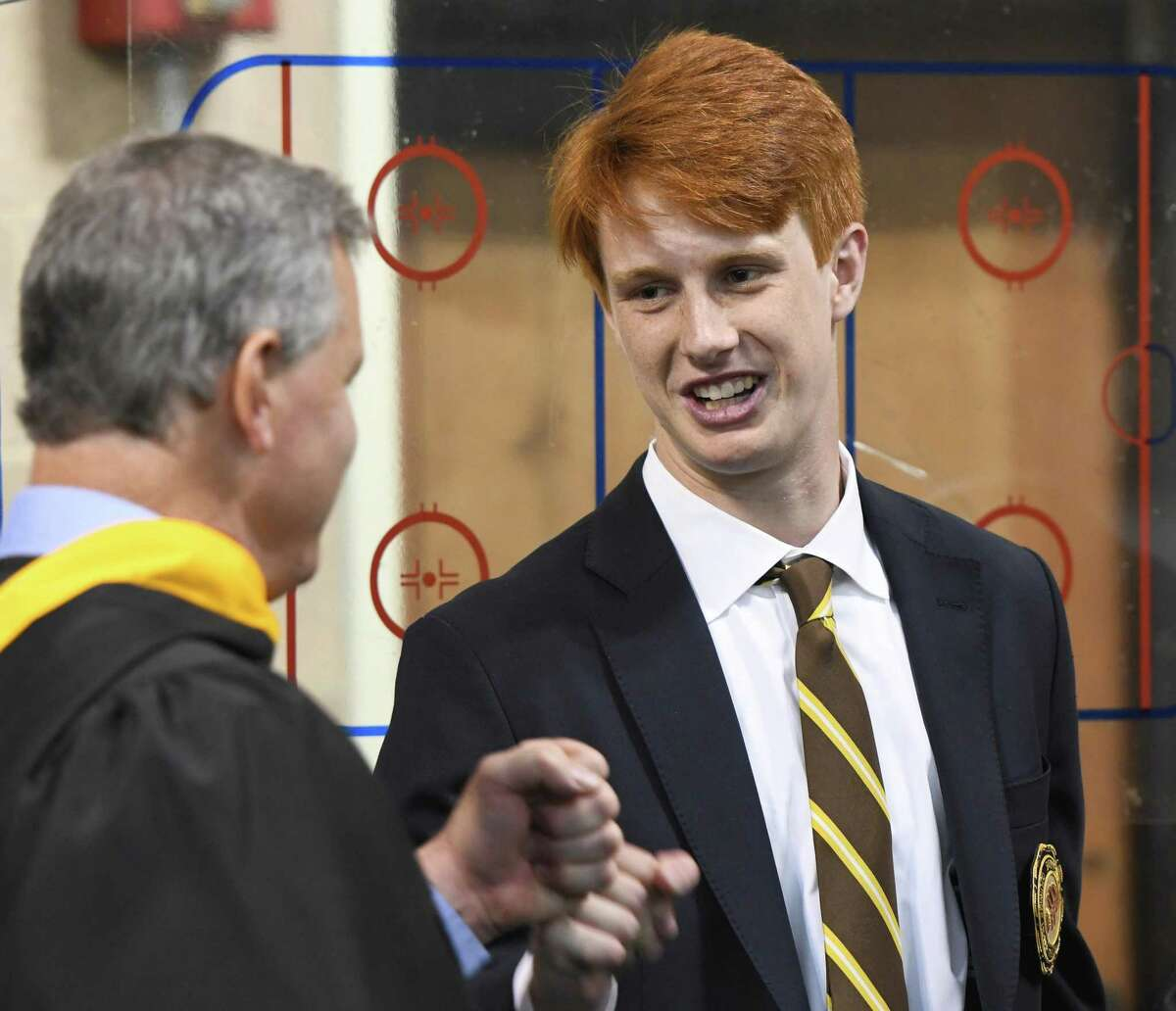 Greenwich's Fin Signer fist-bumps teacher Steve Spolikoff before the Brunswick School 117th Commencement in the Dann Gymnasium.