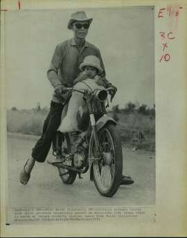 A refugee family with their personal belongings packed on motorbike ride along Route 13 north of Saigon recently fleeing south from North Vietnamese offensive.  Meager belongings were carried in a sack.   South Vietnamese Refugees