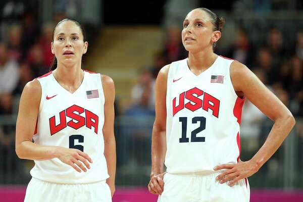 Former UConn teammates Sue Bird (6) and Diana Taurasi (12) take a break in the action against Canada during the 2012 Olympics.