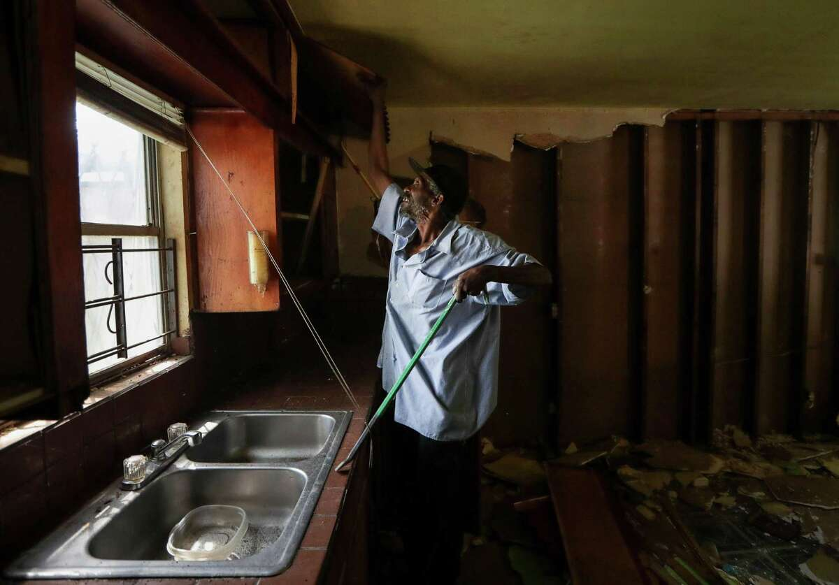 Malberth Moses works to demolish parts of his home that were damaged during Hurricane Harvey.
