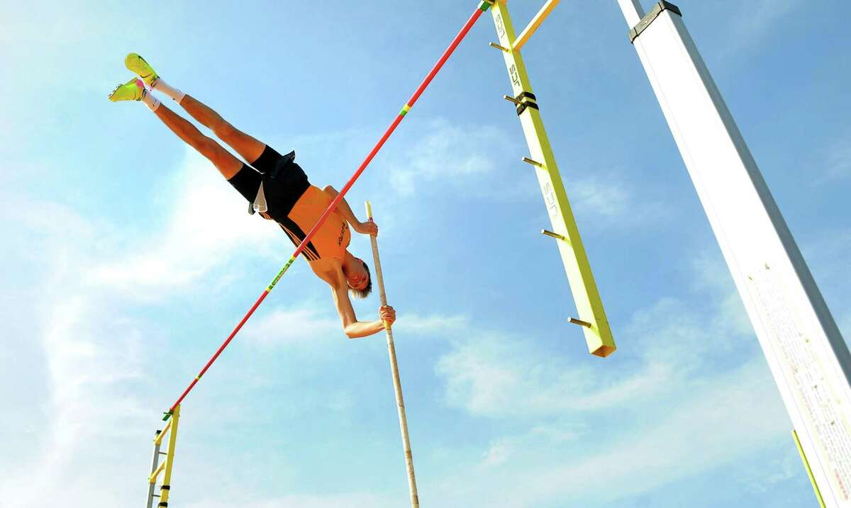 Weston's Chris Lewis clears the bar in the pole vault during SWC Outdoor Track and Field Championship action in Weston, Conn., on Wednesday April 22, 2019.