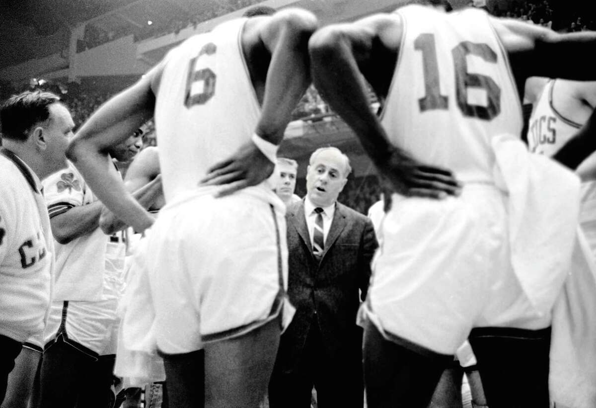 (Original Caption) Celtics' coach Red Auerbach (c) is dwarfed by his charges as he talks to them during time-out, 4th quarter, 1st game, NBA Eastern Division Final Playoffs, Boston Garden. #6, Bill Russell; #16, Satch Sanders; Tommy Heinsohn (L of Auerbach). Celtics won the game, 108-98.